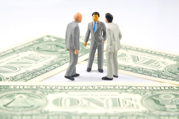 Miniaturowi biznesmeni stoją nad banknotem dolarowym