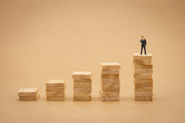 Miniaturowi biznesmeni stojący analiza inwestycji lub inwestycja