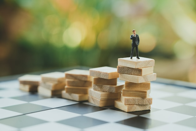 Miniaturowi biznesmeni stojący analiza inwestycji lub inwestycja.