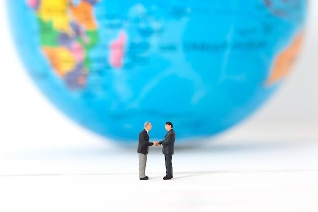Miniaturowi biznesmeni trząść ręki na zamazanym globalnym lub światowym tle.