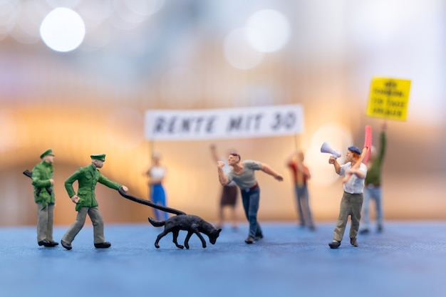 Miniaturowi demonstranci trzymający znaki i protestujący z rozmytym tłem