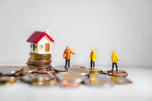 Miniaturowi inżynierowie stoi z mini domem na stosie monet