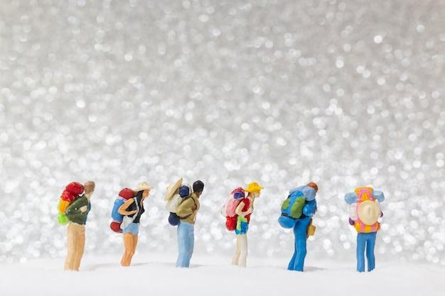 Miniaturowi ludzie, backpacker chodzący po śniegu