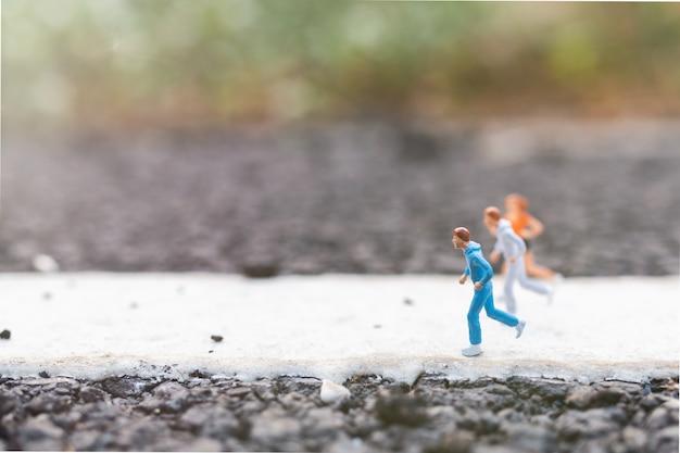 Miniaturowi ludzie biegający na ulicy