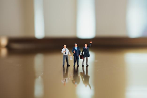 Miniaturowi ludzie, biznes drużynowa trwanie akcja używa jako biznesowej korporaci pojęcie