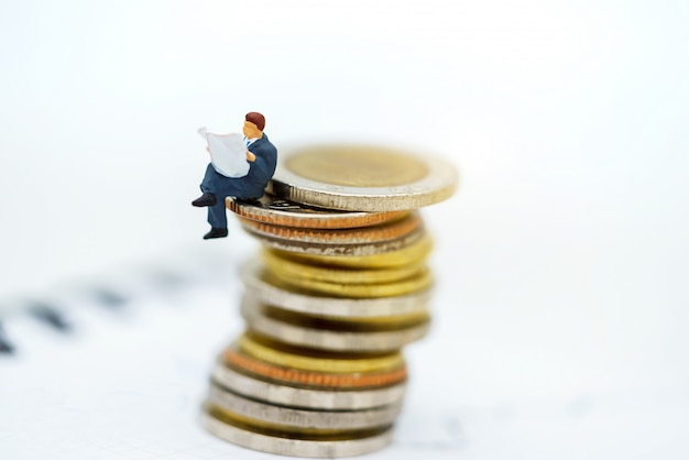 Miniaturowi ludzie: biznesmen czytanie książki na stosie monet.