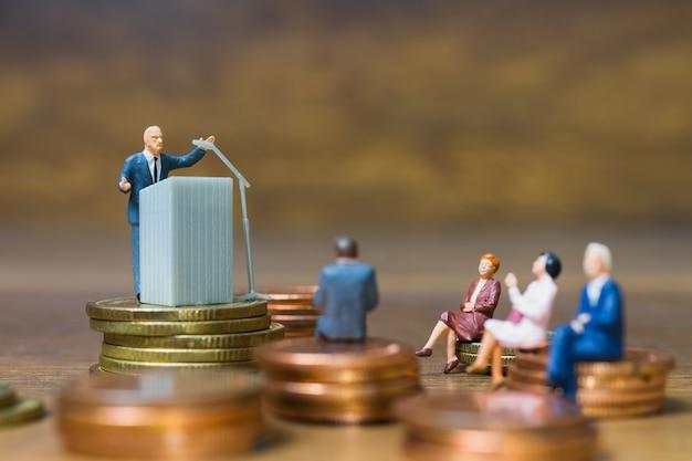 Miniaturowi ludzie: biznesmen mówiąc na podium