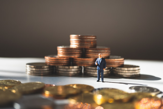 Miniaturowi ludzie, biznesmen pozycja na stercie wyrzucają monety tło