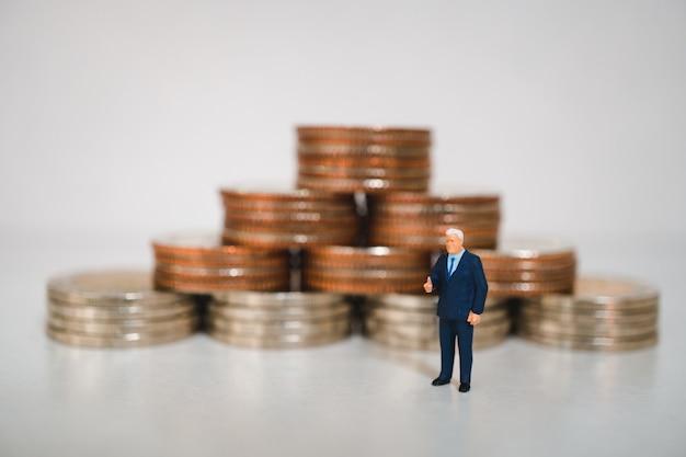 Miniaturowi ludzie, biznesmen pozycja na stosie monet tło