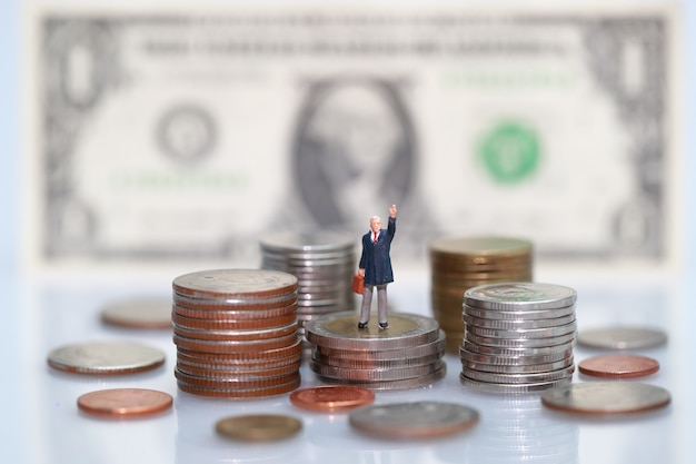 Miniaturowi ludzie: biznesmen pozycja na układać monety