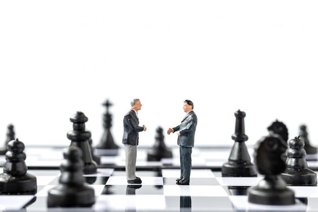 Miniaturowi ludzie biznesmen stoi na szachownicy