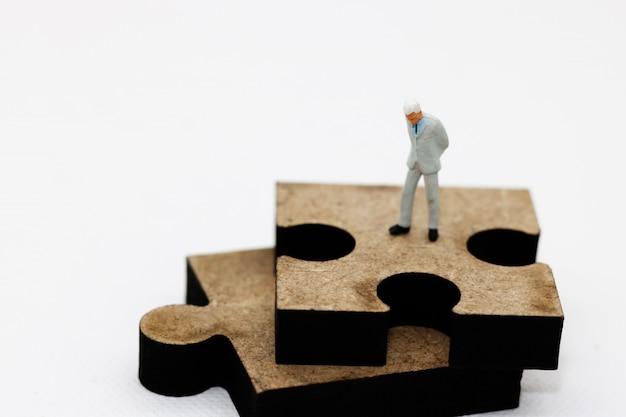 Miniaturowi ludzie: biznesmen stojący na układance