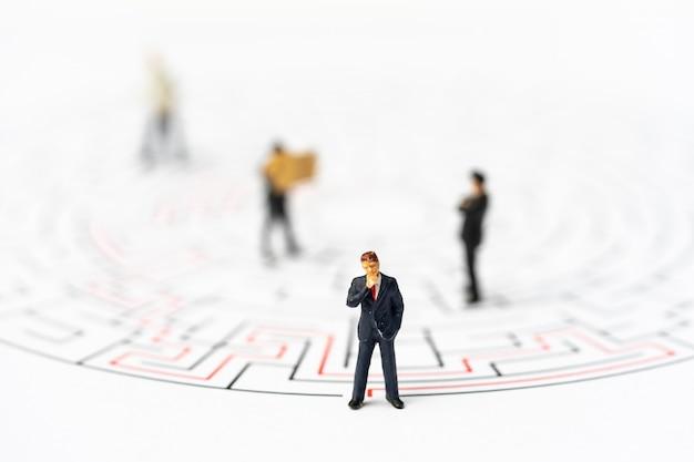 Miniaturowi ludzie, biznesmen w labiryncie lub labirynt zastanawiający się nad wyjściem.