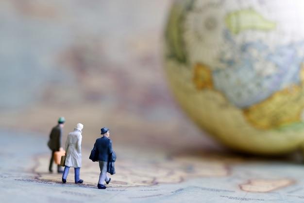 Miniaturowi ludzie, biznesmen z kulą ziemską chodzi do miejsca przeznaczenia na rocznik mapie.