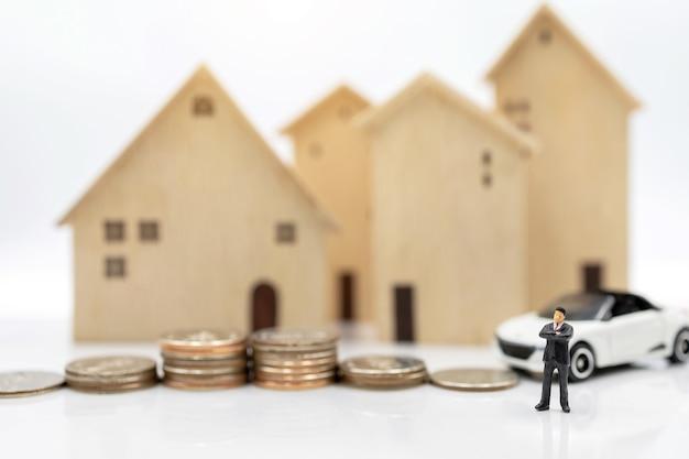 Miniaturowi ludzie: biznesmeni ściskający ręce na stosie monet z domem i samochodem. koncepcja inwestycji mieszkaniowej i samochodowej.