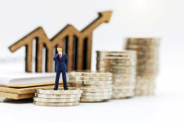 Miniaturowi ludzie: biznesmeni stojący na stosie monet z drewnianym wykresem.