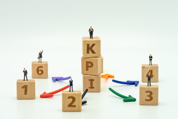 Miniaturowi ludzie biznesmenów stoi na drewnianym słowo kpi personelu kpi