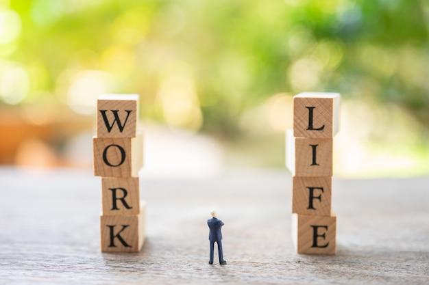 Miniaturowi ludzie biznesmenów stoi z drewnianym słowem praca i życie