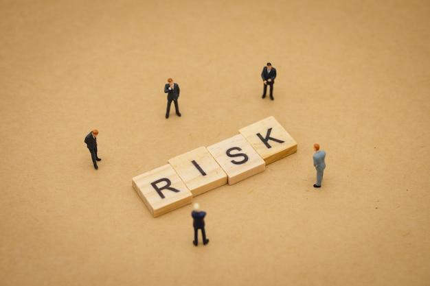 Miniaturowi ludzie biznesmenów stoi z drewnianym słowem ryzyko