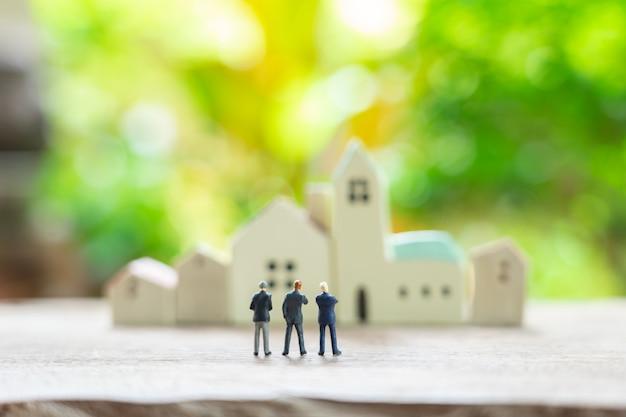 Miniaturowi ludzie biznesmenów stoi z plecy negocjuje w biznesie.