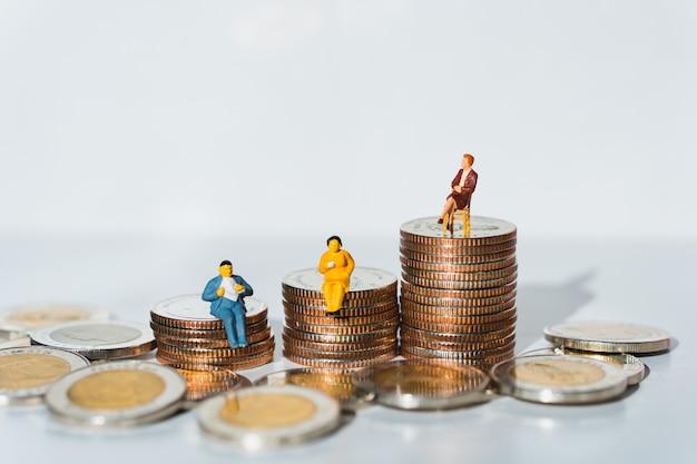 Miniaturowi ludzie, biznesowy drużynowy obsiadanie na stos monetach używać jako biznesowa praca zespołowa i pieniężny pojęcie