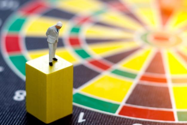 Miniaturowi ludzie biznesu stoi na drewnianym pudełku z dartboard.