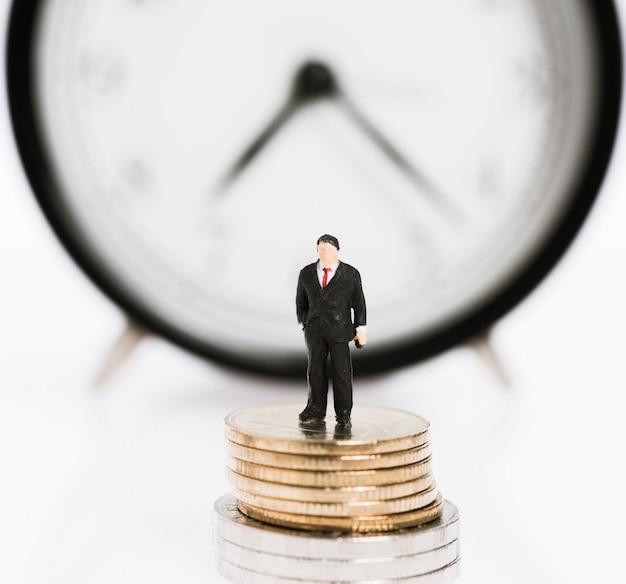Miniaturowi ludzie biznesu stoją na srebrnych monetach z tłem budzika, czas to pojęcie pieniądza