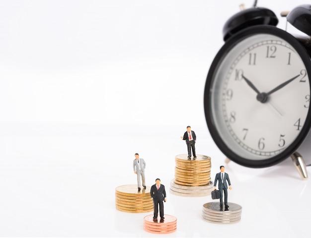 Miniaturowi ludzie biznesu stoją na stosie złotych monet na tle budzika, a zarządzanie czasem przyniosło firmie sukces.