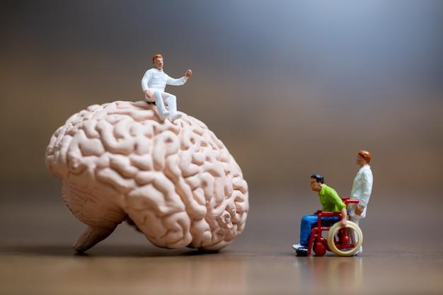 Miniaturowi ludzie, chirurg rozmawiał z pacjentem o urazach mózgu. koncepcja usługi medycznej opieki zdrowotnej i lekarza chirurgicznego.
