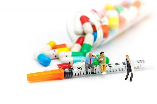 Miniaturowi ludzie: grubi pacjenci siedzi na strzykawce z lekami. pojęcie opieki zdrowotnej.