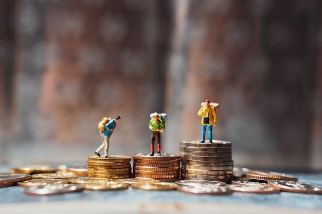 Miniaturowi ludzie, grupa podróżników stojących na stosie monet