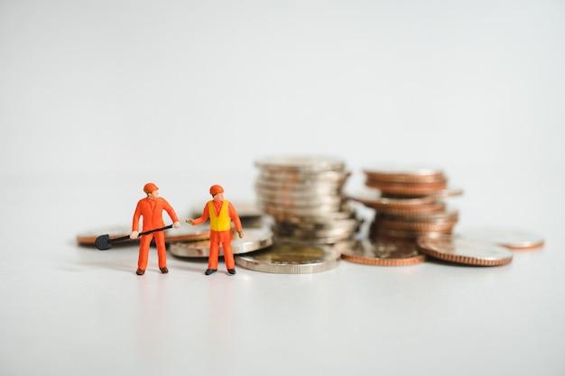 Miniaturowi ludzie, inżyniery pracuje z stert monetami używać jako pieniężny i biznesowy pojęcie