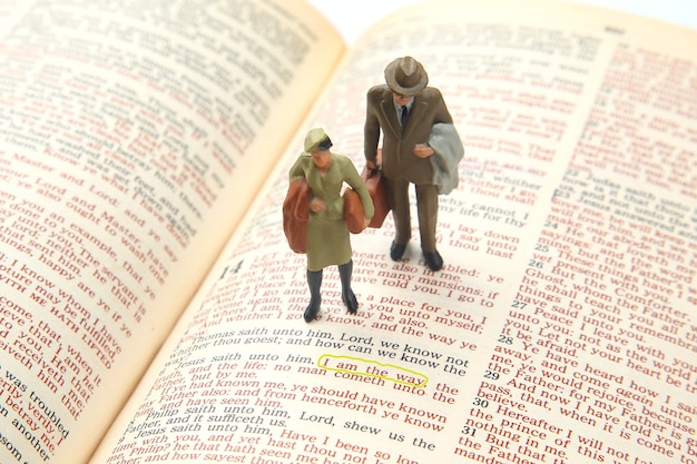 Miniaturowi ludzie. kobieta i mężczyzna stoją na tekście biblijnym. szukać ścieżki życia. jestem drogą.
