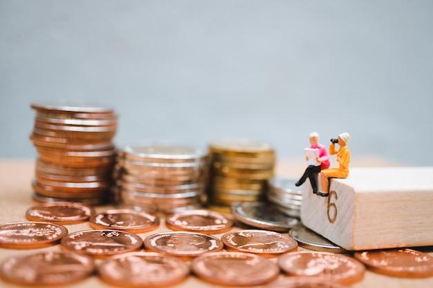 Miniaturowi ludzie, kobiety czytelnicza książka na stos monetach używać jako biznesowy i pieniężny pojęcie