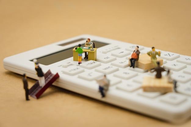 Miniaturowi ludzie kolejka płacowa roczny dochód (podatek) za rok na kalkulatorze.