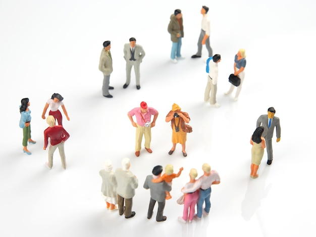 Miniaturowi ludzie komunikują się ze sobą na białym tle