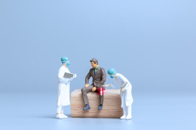Miniaturowi ludzie lekarze leczą reumatyzm, chorobę zwyrodnieniową stawów, koncepcję światowego dnia zapalenia stawów
