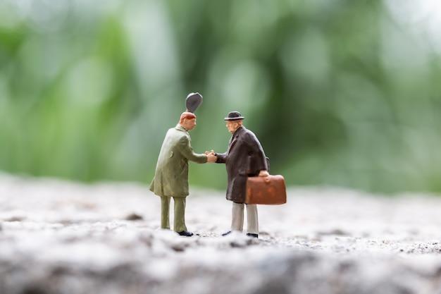 Miniaturowi ludzie: ludzie biznesu spotykają powitanie trząść ręki plenerową scenę