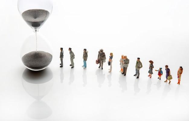Miniaturowi ludzie. ludzie w różnym wieku i różnym statusie stoją w kolejce przy klepsydrze. pojęcie ważności czasu i życia