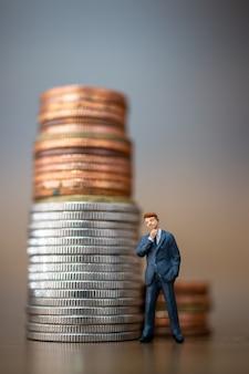 Miniaturowi ludzie: mali biznesmeni stojący ze stosem monet, koncepcja rozwoju biznesu.