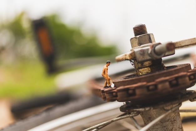 Miniaturowi ludzie: mechanicy naprawiający rower