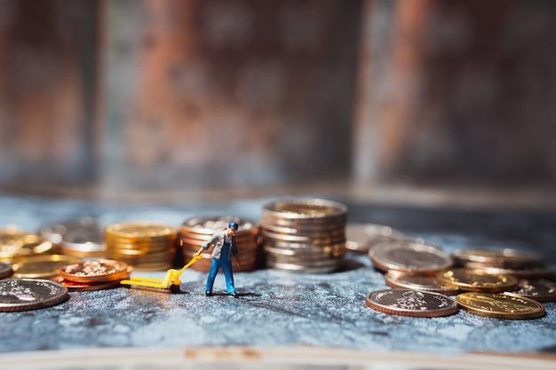Miniaturowi ludzie, mężczyzna ciągnący stos monet