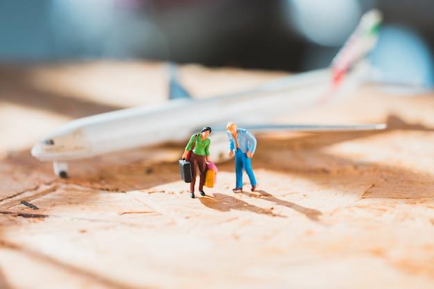 Miniaturowi ludzie, mężczyzna i kobieta chodzą na tle samolotu jako koncepcja podróży i rodziny