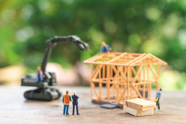 Miniaturowi ludzie naprawa robotników budowlanych model domu modelowego