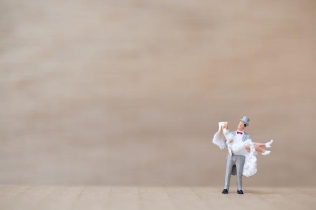 Miniaturowi ludzie: państwo młodzi na drewnianym tle