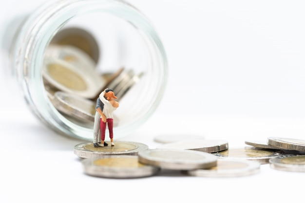 Miniaturowi ludzie, para stoi na stosach monet i słoik monet.