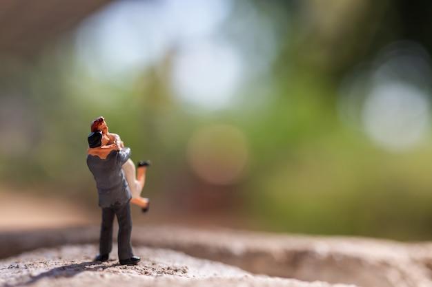 Miniaturowi ludzie: para stoi w parku