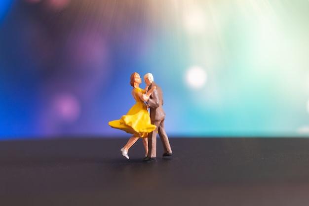 Miniaturowi ludzie, para taniec z kolorowym tłem