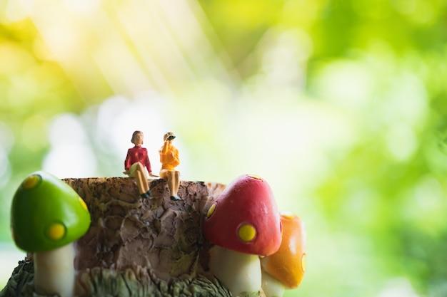 Miniaturowi ludzie, pary kobiety obsiadanie na pieczarkowym szalunku, kobiety obsiadanie na zielonym natury tle