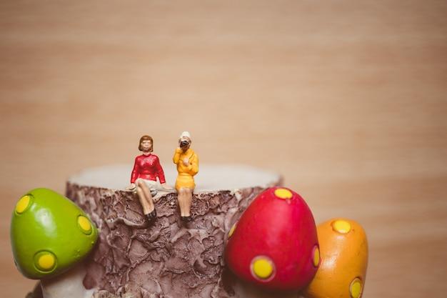Miniaturowi ludzie, pary kobiety obsiadanie na pieczarkowym szalunku używać dla relaksu pojęcia - rocznik fil